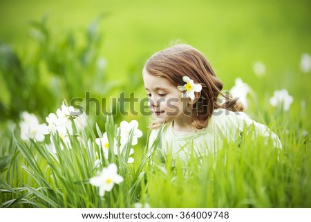 Beautiful little girl smelling flowers.