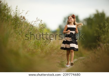 Beautiful little girl smiling and running through a summer outdoors. Adorable young girl running.  - stock photo