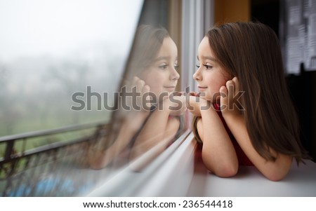 Beautiful little girl smiling and watching out the window. A child looks out the window. Young girl looking from window. Portrait of cheerful kid sits at window. - stock photo