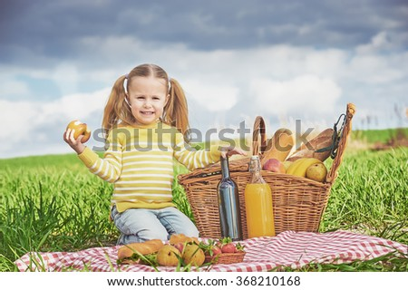 Beautiful little girl smiling doing a picnic on the green spring grass.