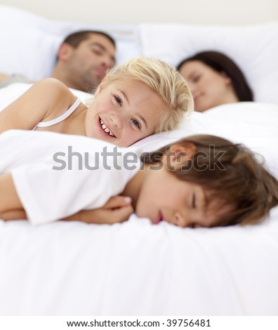 Beautiful little girl smiling on bed wile her family sleep - stock photo