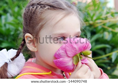 Beautiful Little Girl Sniffs Peony Flower in a Garden - stock photo