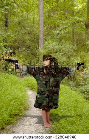 Beautiful little girl soldier with a gun - stock photo