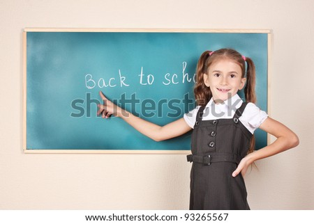 beautiful little girl standing near blackboard in the classroom - stock photo