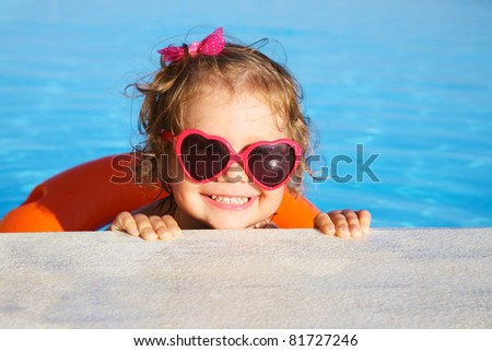 Beautiful little  girl sunning at the pool