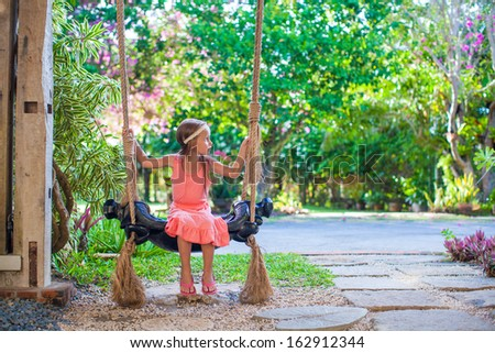Beautiful little girl swinging on a swing in a cozy lovely flowered courtyard - stock photo