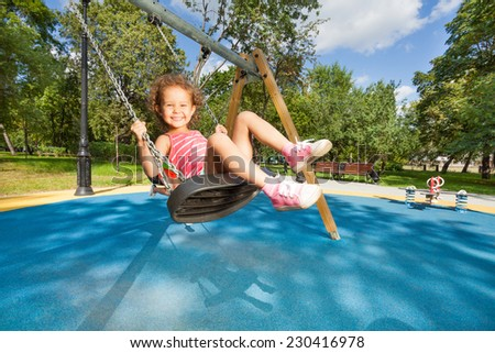 Beautiful little girl swinging on the playground with big nice toothy smile on sunny day - stock photo