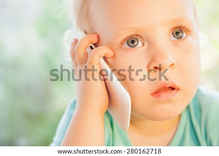 Beautiful little girl talking by mobile phone with her mother. She is blonde with very beautiful eyes on a green background - stock photo