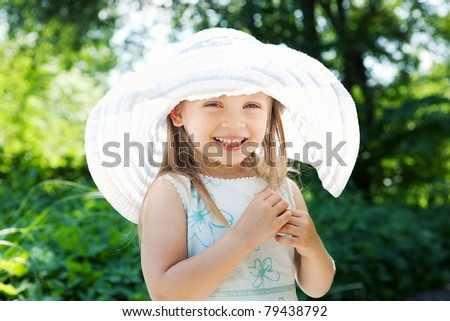 Beautiful little girl wearing a white hat outdoors at the park - stock photo