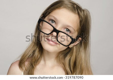 Beautiful little girl wearing big eyeglasses and looking smart