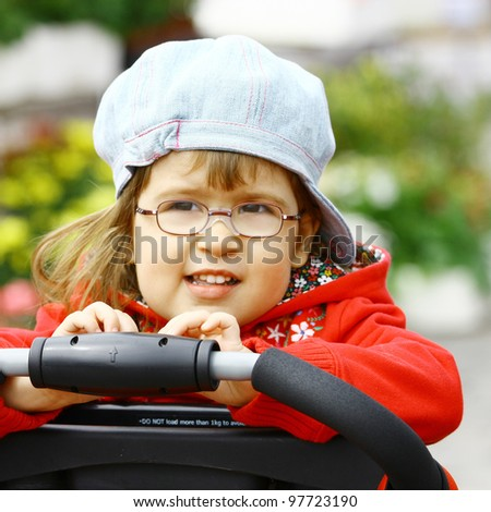 Beautiful little girl wearing glasses 3 years old in denim jeans cap and red jacket - stock photo