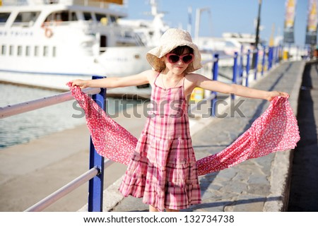 Beautiful little girl wearing pink dress, hat and sunglasses is ready for beach vacation - stock photo