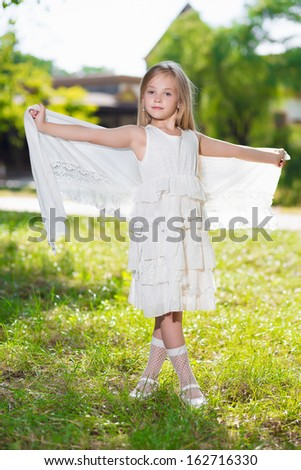 Beautiful little girl wearing white dress posing outdoors - stock photo