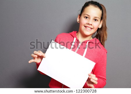 Beautiful little girl with a lovely smile holding up a blank sheet of paper at a tilted angle in her hands - stock photo