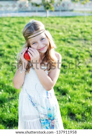 Beautiful little girl with a red apple on grass