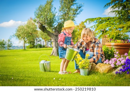 Beautiful little girl with a smile helps his mother in the work of gardening. - stock photo