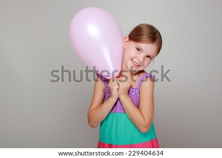 Beautiful little girl with a sweet smile holding a pink air balloon on Holiday