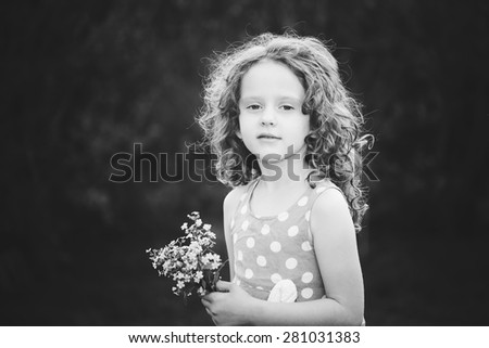 Beautiful little girl with a wildflower in her hand. Black and white photo.