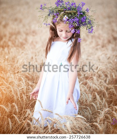 beautiful  little girl with a wreath on his head in a field of wheat - stock photo