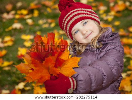 Beautiful little girl with autumn leaves - stock photo