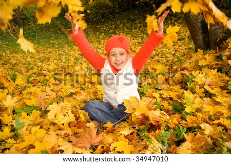 Beautiful little girl with autumn leaves outdoors - stock photo