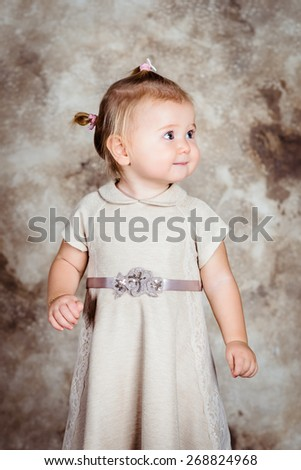Beautiful little girl with blond hair and plump cheeks wearing stylish beige dress
