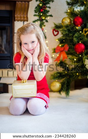 Beautiful little girl with blond hair, dressed in a red dress, sits near a Christmas tree and fireplace with hands on her cheeks. Christmas Eve. - stock photo