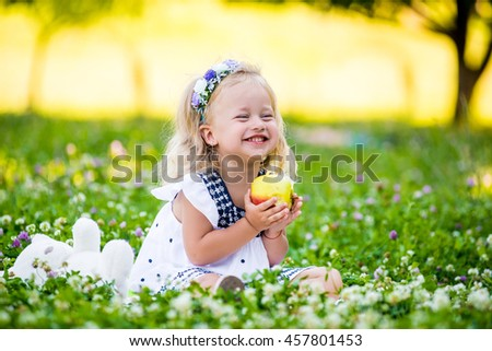 beautiful little girl with blond hair eating an apple in the park