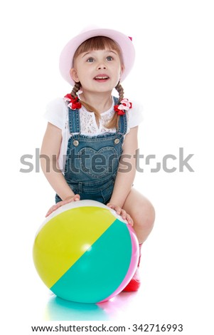 Beautiful little girl ,with blond pigtails on her head in a pink hat and denim overalls stands on the knee and keeps the floor around a large inflatable striped ball - Isolated on white background