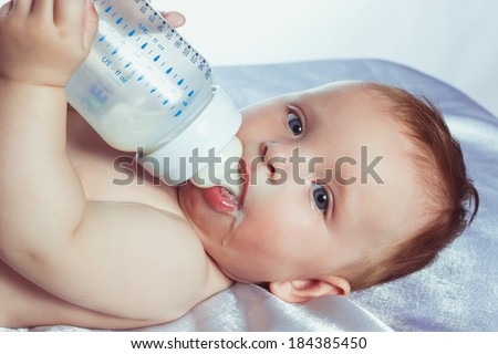 beautiful little girl with blue eyes lying on her back in diapers and drinking milk from a bottle
