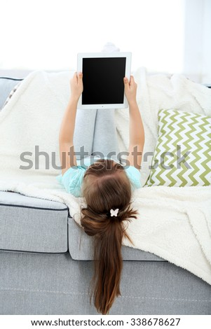 Beautiful little girl with digital tablet sitting on sofa, on home interior background
