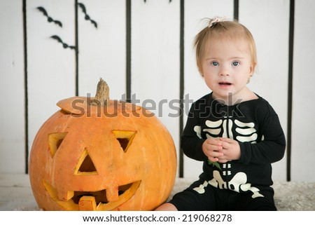 beautiful little girl with Down syndrome sitting near a pumpkin on Halloween dressed as a skeleton