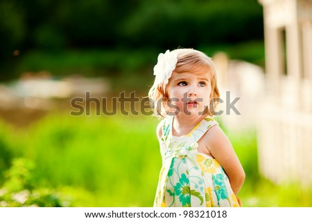 Beautiful little girl with flower on her head outdoors in sunny day - stock photo