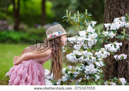 Beautiful little girl with flowers outdoor - stock photo