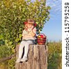 Beautiful little girl with fruits in basket at garden, sitting on wooden hemp - stock photo