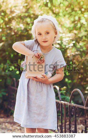 Beautiful little girl with gift package in a summer park