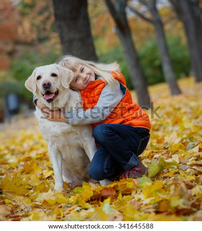 Beautiful little girl with her dog labrador retrievers outdoor in autumn beautiful park