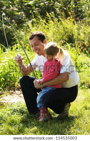 beautiful little girl with her father with a fishing rod in rubber boots