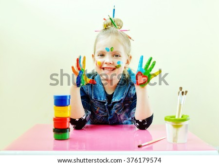 beautiful little girl with her hands in the paint - stock photo