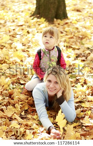 beautiful little girl with her mother in the autumn forest