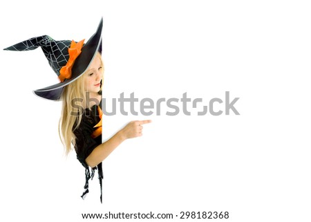 Beautiful little girl with long blonde hair in the witch costume holding a sign. Black witch hat with web, spider and orange bow. Copy space - stock photo