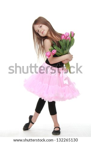 Beautiful little girl with long hair in a pink tutu holding a bouquet of pink tulips - stock photo