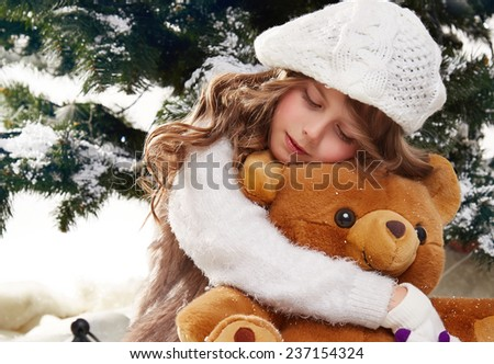 Beautiful little girl with long hair in a white winter sweater sits in the snow at Christmas trees and hugging a teddy bear gift for New Year lantern with a candle - stock photo