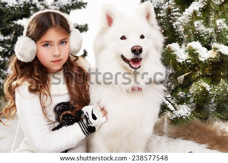 Beautiful little girl with long hair in a white winter sweater sits in the snow at Christmas trees and embraces a large white dog Siberian Husky gift for New Year lantern with a candle - stock photo