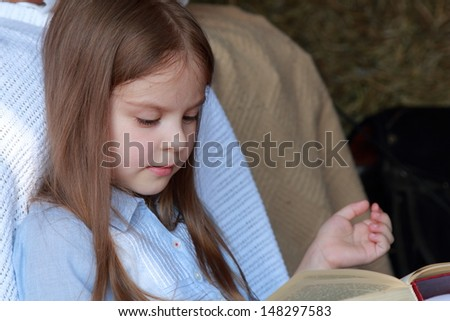 Beautiful little girl with long hair reading a book in the hayloft on a horse farm