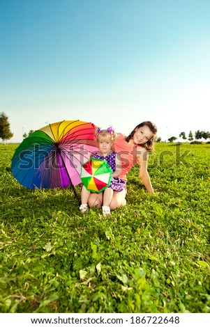 Beautiful little girl with mother rainbow umbrella holding  in  the park. Smiling child and mom on a field with flowers. Kid with mum rest on the  nature. Family outdoor - stock photo