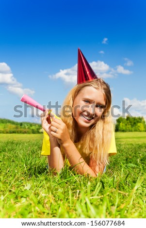 Beautiful little girl with noisemaker horn and birthday party cap laying outside with happy expression on sunny summer day - stock photo
