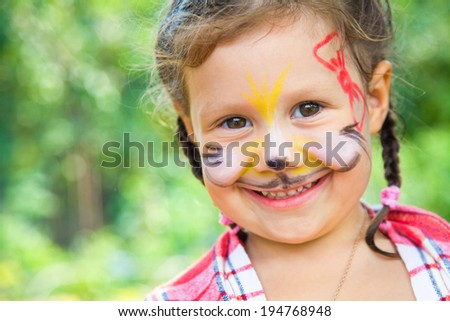 Beautiful little girl  with painted cat on her face - stock photo