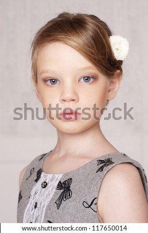 beautiful little girl with perfect makeup and hair-dress with flowers looking at you