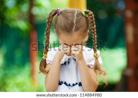 Beautiful little girl with pigtails crying, against background of summer park. - stock photo
